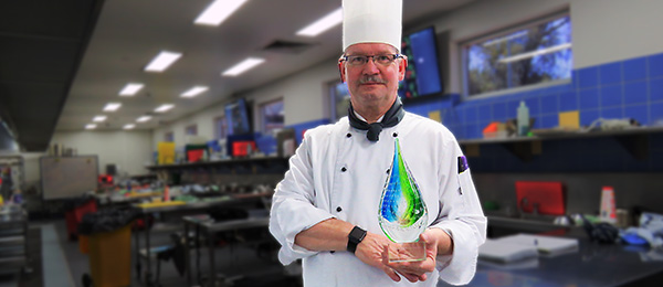 Ingolf Eigenwillig in the Alice campus training kitchen with the Austafe legend's trophy presented to him last year