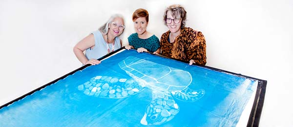 Visual Arts students Jane Anderson, Allyce Peckett and Coordinator of the Bachelor of Creative Arts Sarah Pirrie inspect one of the Catchlight images