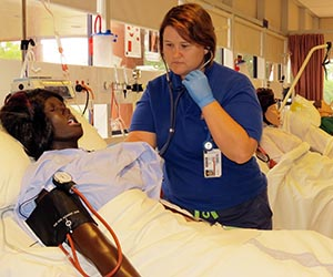 Bachelor of Nursing student, Candice Hatch, examines one of the mannequins