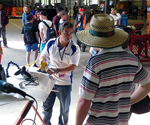 Trades team leader Jamie Finn talks to a member of the public about automotive repair techniques at the Red CentreNATS