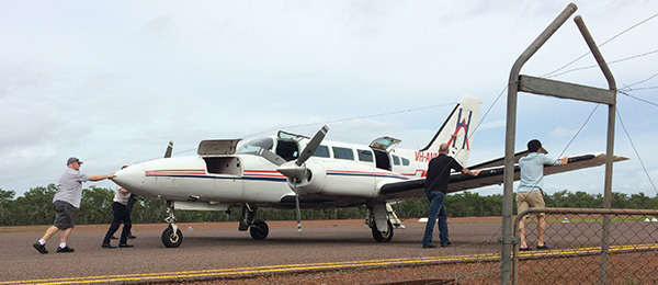Remote health workers move an aircraft on the airstrip in Palumpa in the Northern Territory.