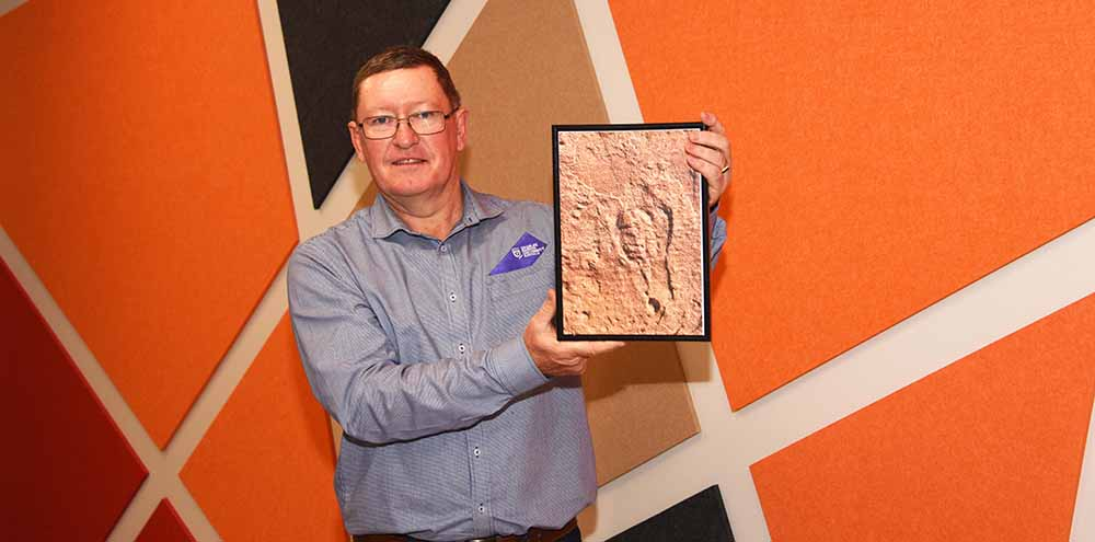 Patrick Nelson holding a picture of the rare fossil he discovered in Central Australia