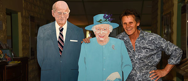 Art teacher Henry Smith (right) breaks protocol by giving the Queen a shoulder squeeze