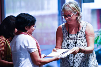 CDU Art Gallery curator Joanna Barrkman presents catalogues to Timor-Leste special guests Cecilia Assis and Rosalia Soares