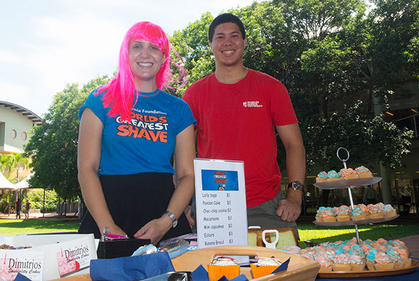Community engagement officer Sierra Bath and student ambassador Patrick Chin help raise money with a smile