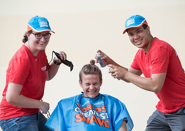 Student ambassadors April Payne and Patrick Chin eye off Augustine Thorbjornsen's top bun