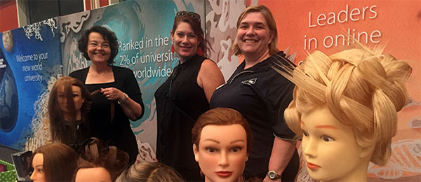 Hairdressing trainer Monika Bloedorn (left) and Tanya Weatherstone (right) discuss hair and beauty courses with visitor Sarah Cook at the expo in Alice Springs