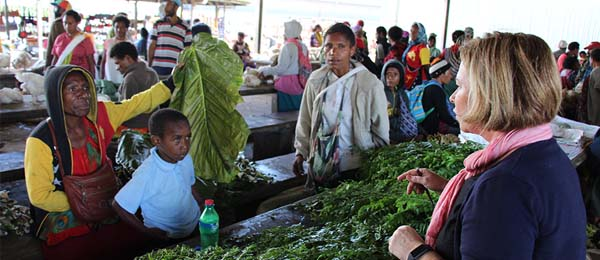 Tania Paul talks to a stall holder selling traditional vegetables used for wrapping pork and fern tips in Mt Hagen's main market