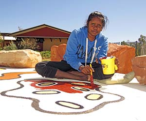 Student Delwyn Williams painting the Yarning Circle in Alice Springs
