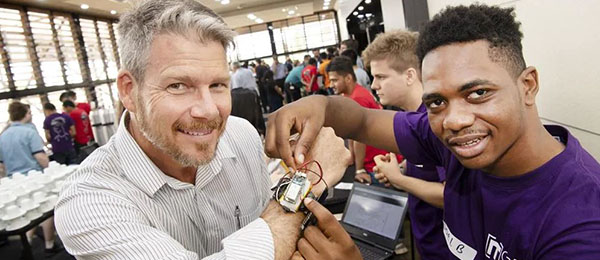 Bachelor of Software Engineering graduate Joel Benesha (right) and David Bradley show off a prototype of the smart watch at the CDU IT Code Fair last year