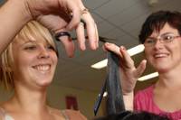 Hair dressing student cutting hair