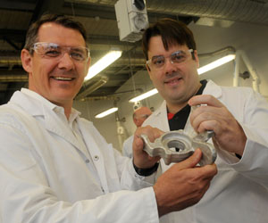 Chief Minister Michael Gunner (left) and Steven Camilleri, inventor of the LightSPEE3D Printer. Steven holds an automotive part produced by the printer.