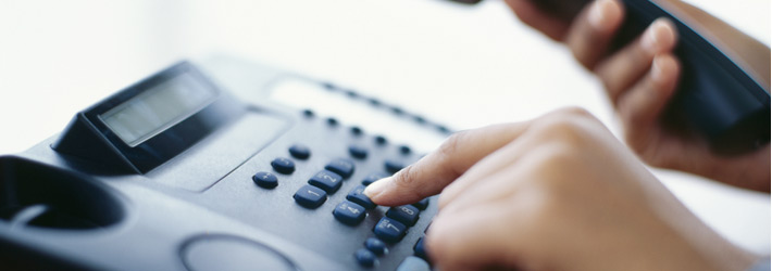 close up image of hand dialing a number on the telephone