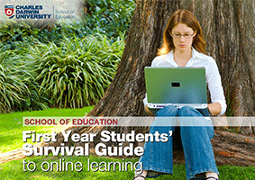 Student studying outside under tree with laptop