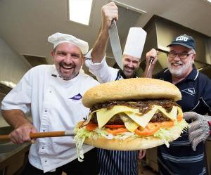 Charles Darwin University VET Culinary Arts lecturers, baker Robert Schwerdt, chef Jason Wilkes, and butcher Rodney Sims practising for Sunday's attempt to cook the Territory's biggest burger.