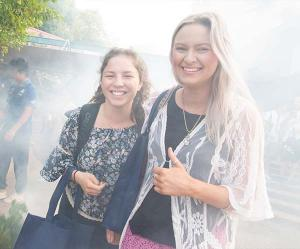 New CDU Psychology students Emmy Lang and Jacquelyn Agustin enjoy a traditional smoking ceremony as part of the university's Semester 2 Orientation activities