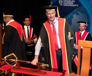 The Hon Paul Henderson AO, with his hand on the university mace, formally takes on the role of Chancellor of Charles Darwin University.
