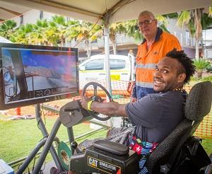 Jerimus Dimpamala tests his skills at the new dump truck simulator at CDU Open Day. Pictured with VET lecturer Peter Bacon