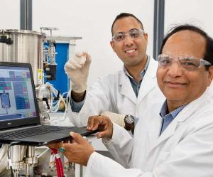Hooman Mehdizadeh Rad showing the NT's first organic solar cell with Professor Jai Singh AM.