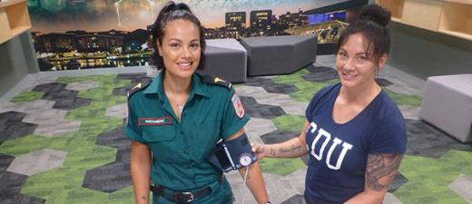 St John NT paramedic Gabriella Edwards (left) was on hand to assist CDU paramedicine student Laanie Wright with her studies as part of the Bachelor of Paramedicine course
