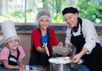 Lecturer Tracey Poelsma helps to dust meringue mixture with participants Gemma Hinds and Emma Stewart