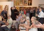 A crowd applauds the artist at the exhibition opening